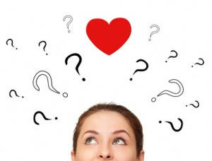 Girl thinking about love with many questions and heart above